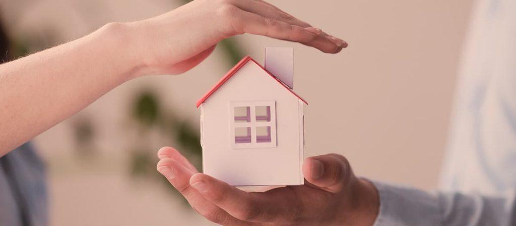 Duas pessoas segurando uma pequena casa simbolizando a segurança de condomínios.