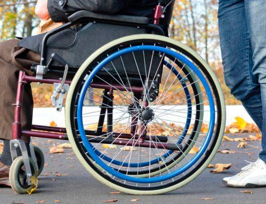 Pessoa auxiliando outra que está usando uma cadeira de rodas.