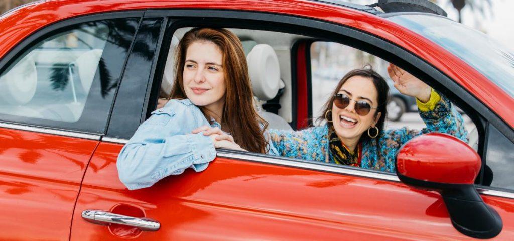Duas mulheres dentro de um carro vermelho.