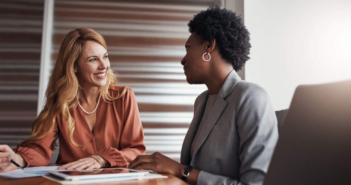 Conversa entre duas mulheres, ambas estão felizes.
