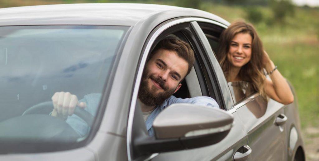 Duas pessoas felizes em um carro, estão na janela, ambos felizes.