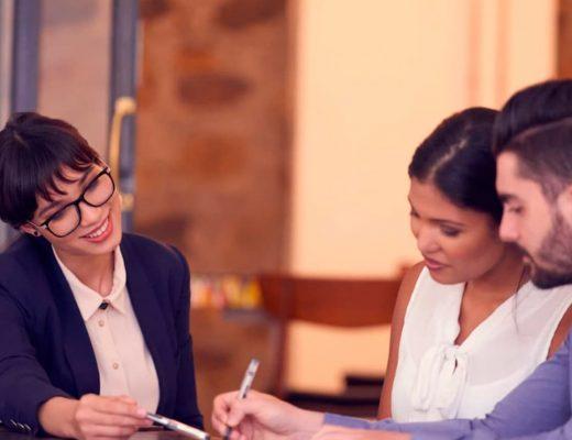 Conversa entre três pessoas, uma reunião, duas estão assinando algo.