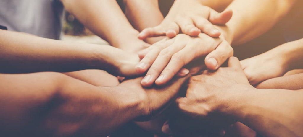 Grupos com as mãos sobrepostas.