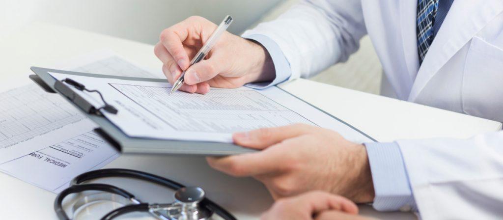 Medico escrevendo em sua prancheta.