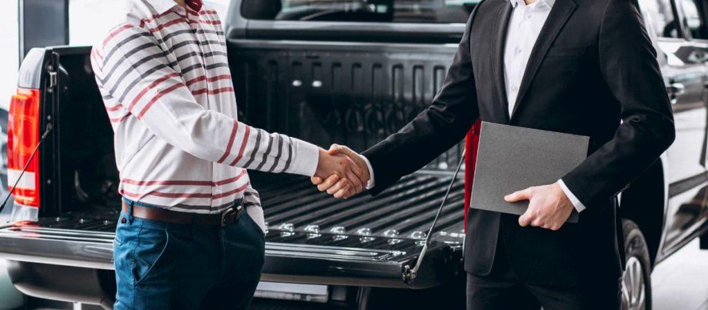 Duas pessoas apertando as mãos. Fechando um contrato de seguro frotas de veículos