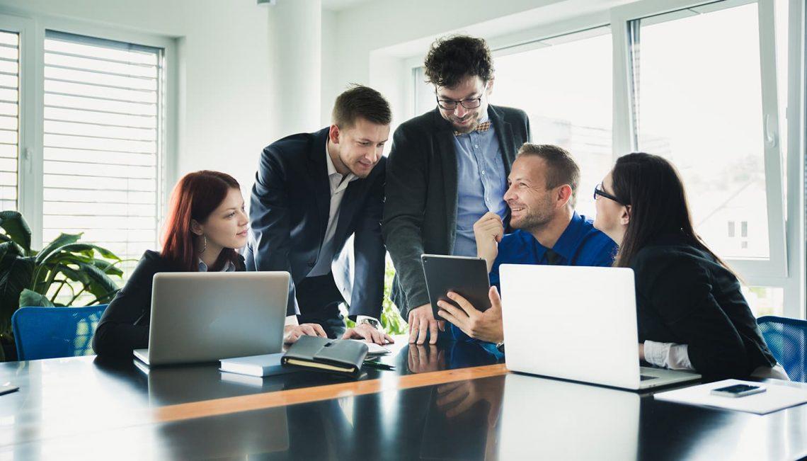 Reunião entre cinco pessoas, estão todos olhando para um tablet, ambos felizes.