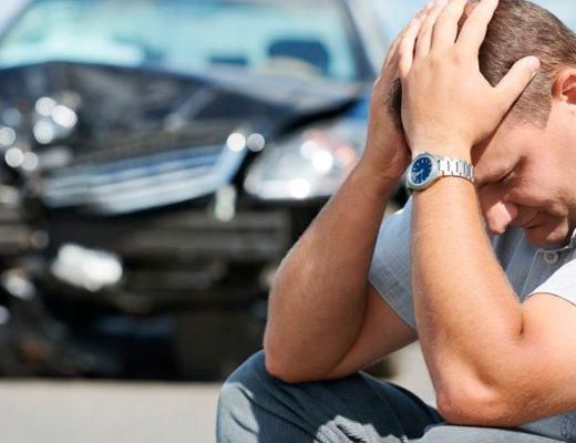 Homem frustado com a batida de seu carro.