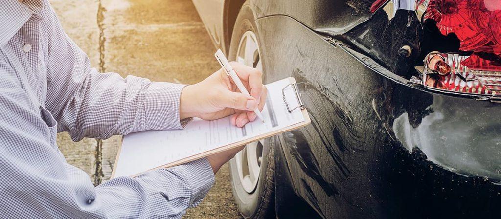Homem analisando e anotando estragos sobre um carro.
