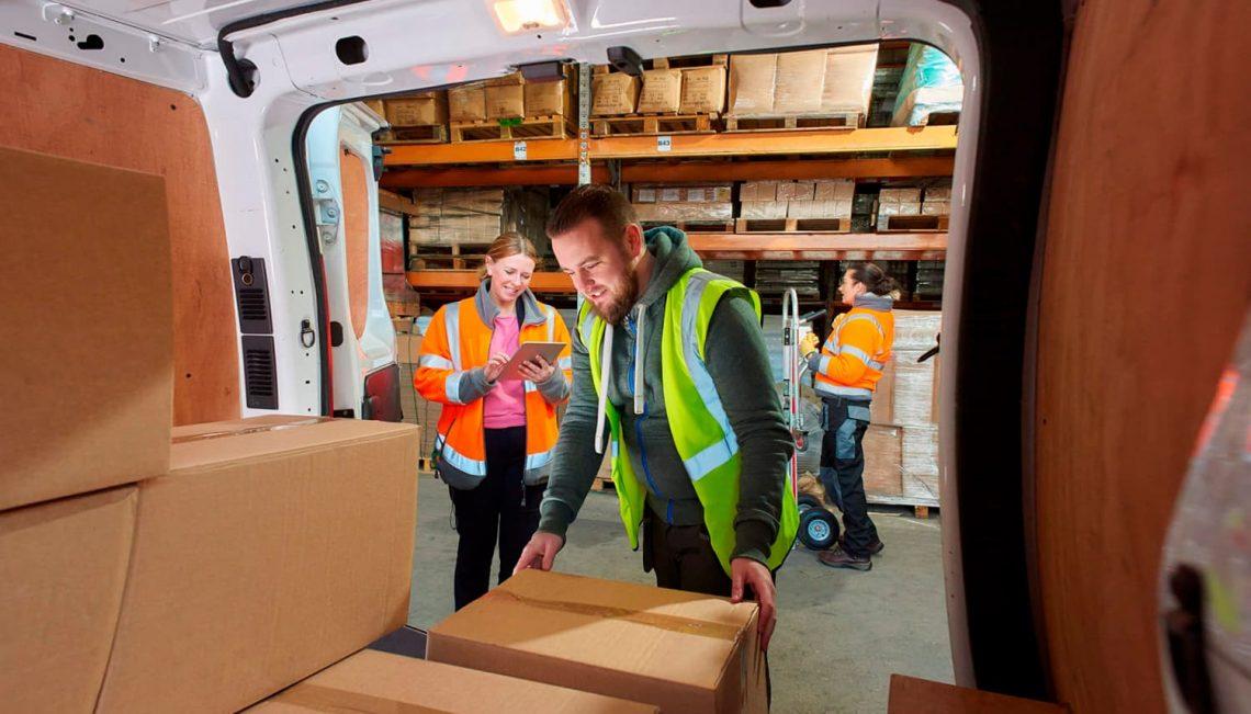 Duas pessoas analisando caixas que estão dentro de uma van, antes de serem entregues.