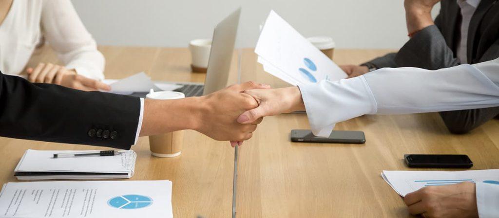Várias pessoas em uma mesa estão em uma reunião, duas está dando um aperto de mão.