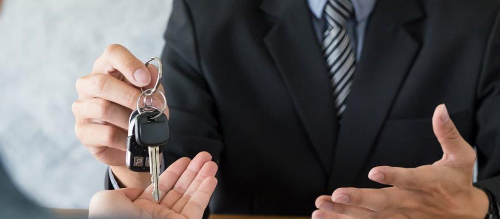 Homem entregando chave de um carro para seu cliente.