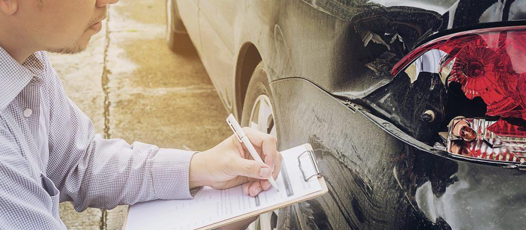 Homem anotando estragos causados em um carro.