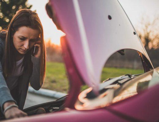 Mulher olhando algo no motor do carro e conversando com alguém no celular.
