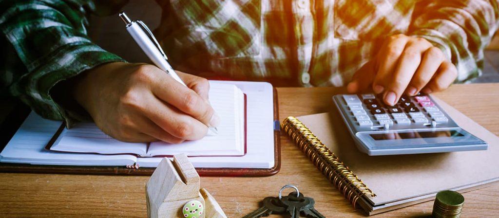 Homem segurando uma caneta em cima de uma folha quanto usa uma calculadora.
