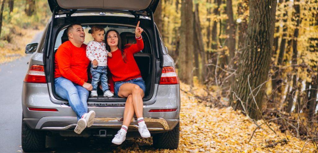 Família sentada no porta malas de um carro em uma viagem estão todos felizes.
