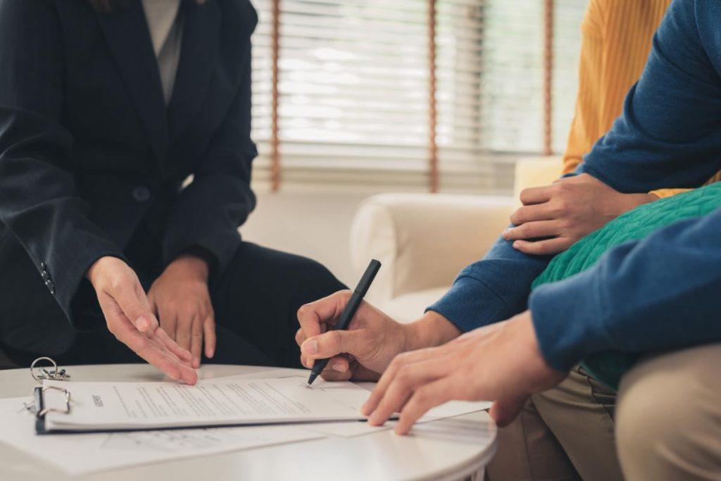 Pessoa assinando um contrato enquanto a outra aponta para algo no contrato.