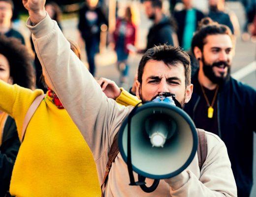 Várias pessoas se manifestando em uma rua publica.