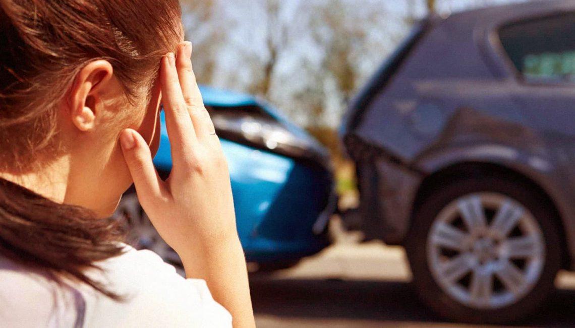 Mulher chateada vendo seu carro batido