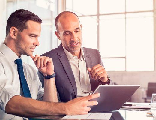 Dois homens conversando e olhando para o tablet.