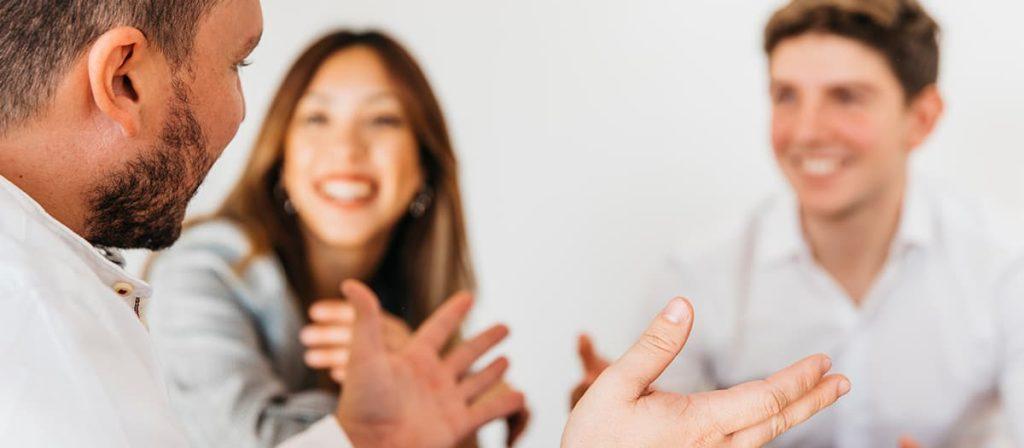 Conversa feliz entre três pessoas.