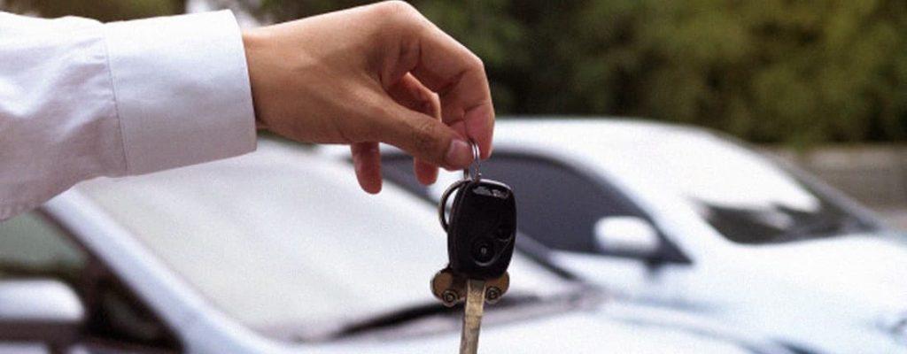 Pessoa segurando a chave de um carro.