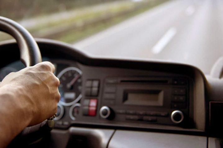 Motorista dirigindo um caminhão de cargas. Só aparece a mão na direção e a estrada à frente.