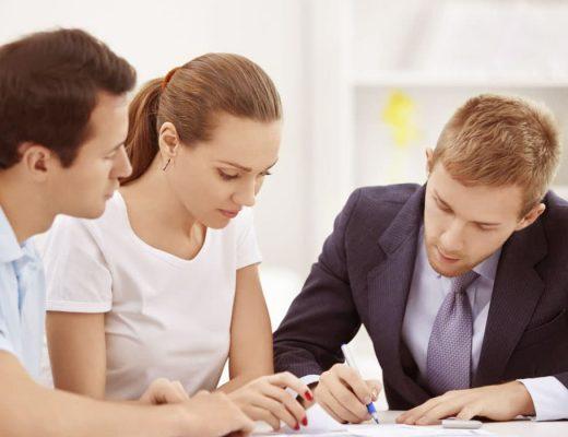 Dois homens e uma mulher discutindo sobre uma proposta de seguro patriminial sobre a mesa.