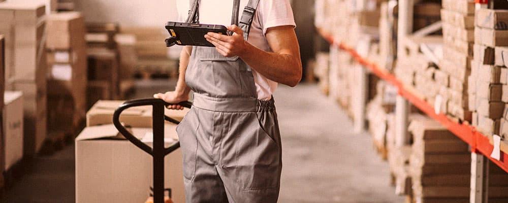 Uma pessoa dentro de um armazém olhando um texto sobre seguro para veículos de transportadoras.